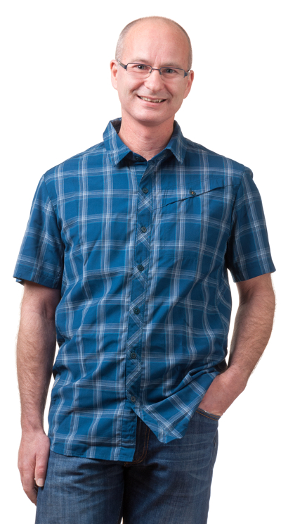 Mike wearing a blue check shirt smiling at camera