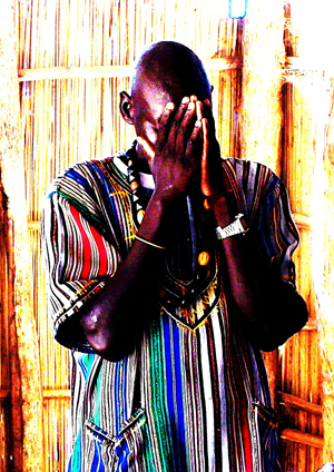 Ugandan man in brightly shirt praying