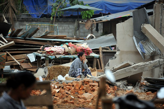 Burmese woman sitting in the rubble of an earthquake damaged house
