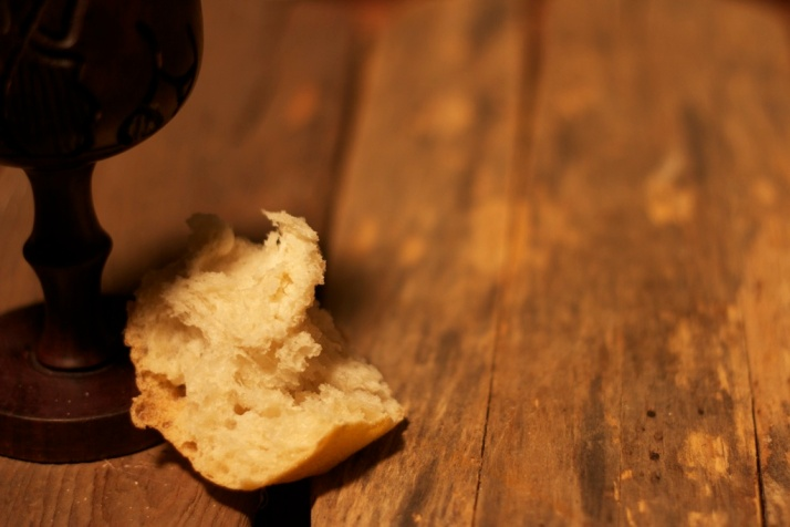 a crust of communion bread and wine goblet on a wooden table