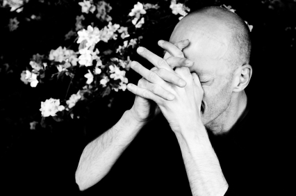 caucasian man praying with hands over his face