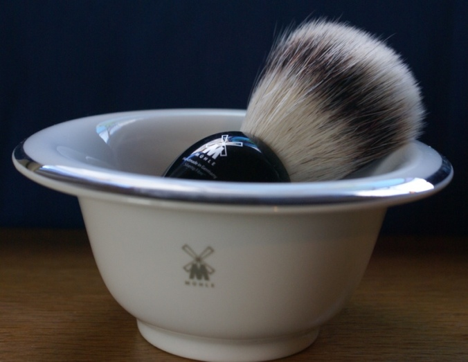 photo of a white ceramic shaving bowl with gold rim and a black synthetic badger hair shaving brush in the bowl