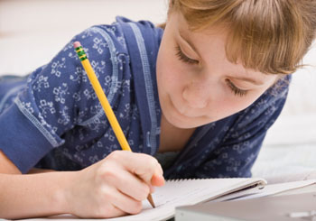 A young girl writing in a notebook.