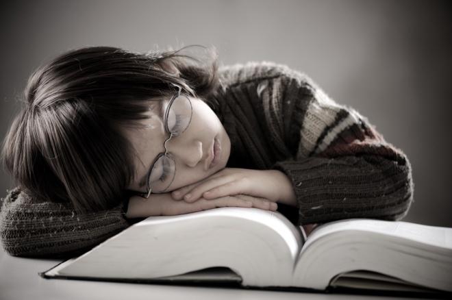 boy asleep on a big book