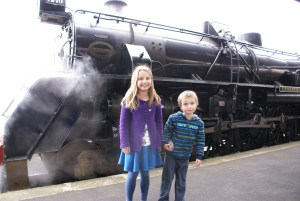 Standing beside steam engine